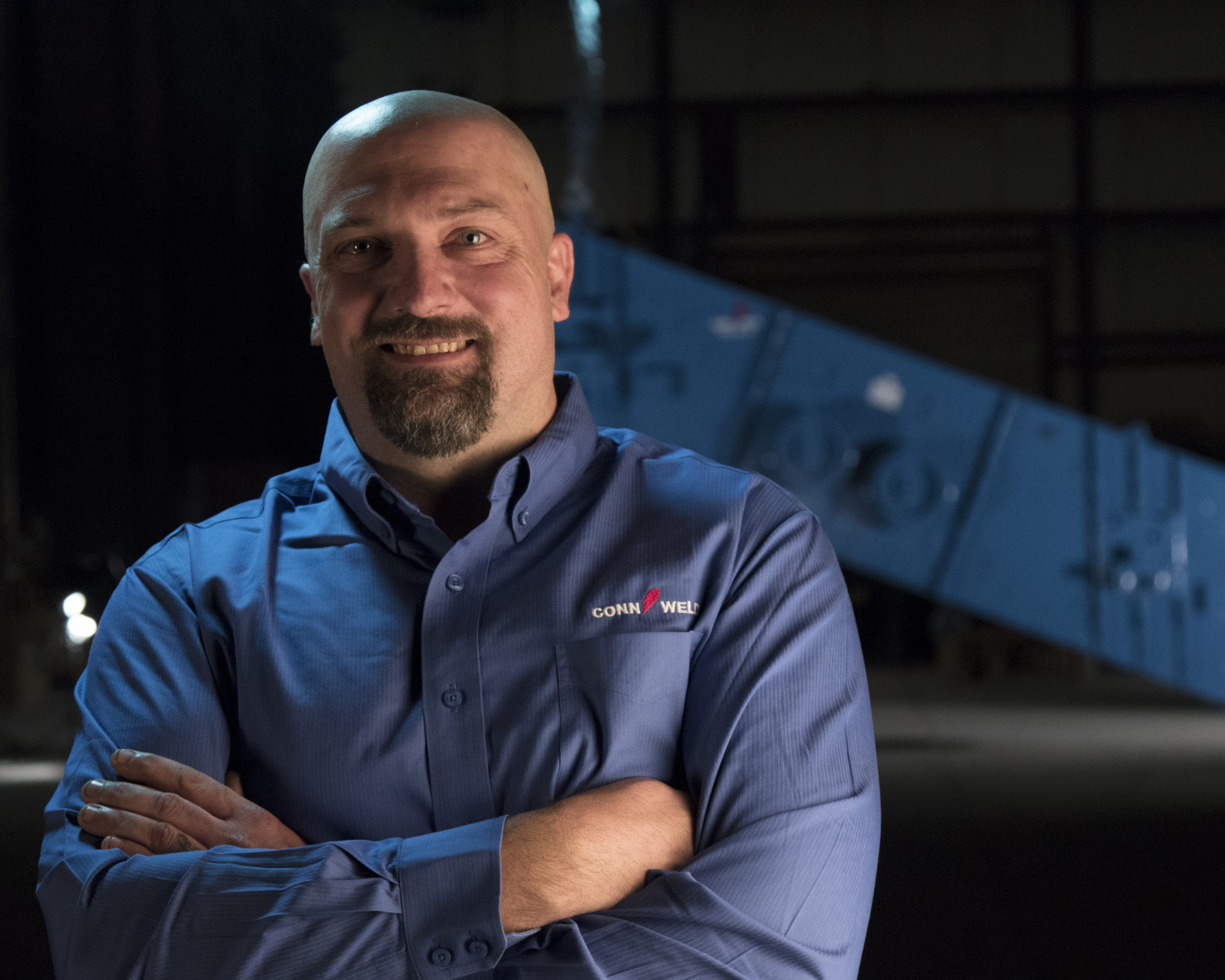 Conn-Weld man in blue shirt arms crossed smiling